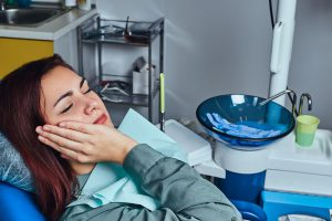 young-woman-suffering-from-a-toothache-while-sitti-ZEG9SKH (1)