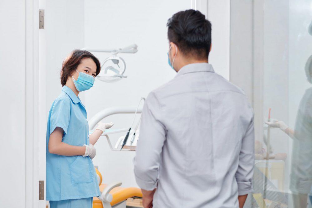 dental-nurse-inviting-patient-ESXZZV3