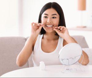 young-asian-lady-using-dental-floss-recording-vlog-DKWBCU3